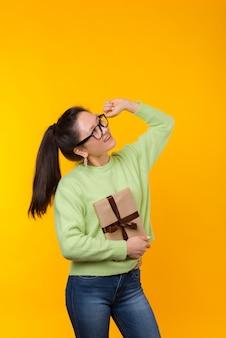 De gelukkige status op gele vrouw houdt een gift zoals een boek
