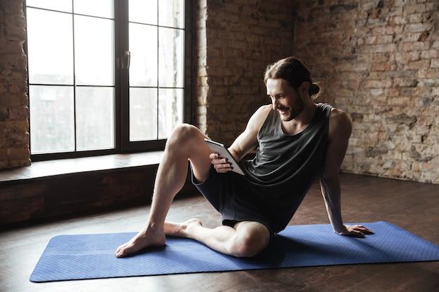 De gelukkige sterke sportman ligt bij vloer het babbelen door tablet
