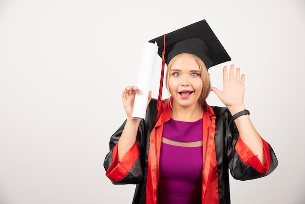 De gelukkige student in toga ontving diploma op witte muur.