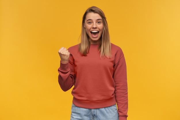 De gelukkige succesvolle jonge vrouw in vrijetijdskleding toont winnaargebaar en schreeuwend over gele muur.