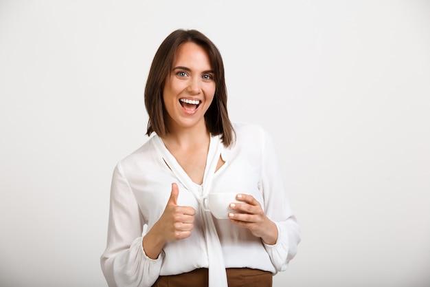 De gelukkige succesvolle vrouw thumbs-up, geeft goedkeuring, drinkt koffie