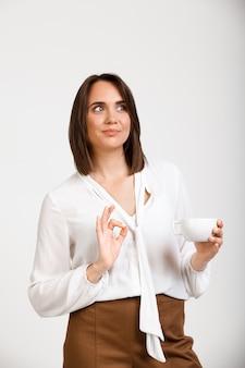 De gelukkige succesvolle vrouw toont ok, geeft goedkeuring, drinkt koffie