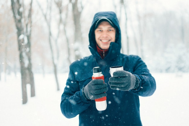 De gelukkige thermosfles van de mensenholding in de winterpark