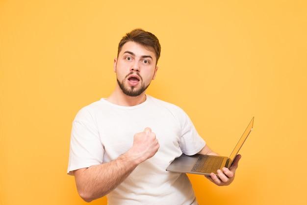 De gelukkige tiener in een wit t-shirt houdt de laptop in zijn handen
