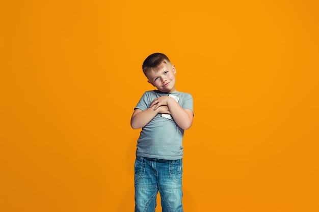 De gelukkige tienerjongen die en tegen sinaasappel bevindt zich glimlacht.