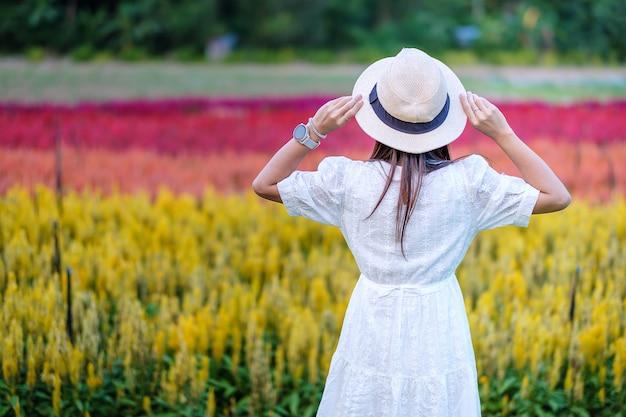 De gelukkige toeristenvrouw in witte kleding geniet van de prachtige bloementuin.