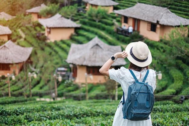 De gelukkige toeristenvrouw in witte kleding geniet van prachtige theetuin.