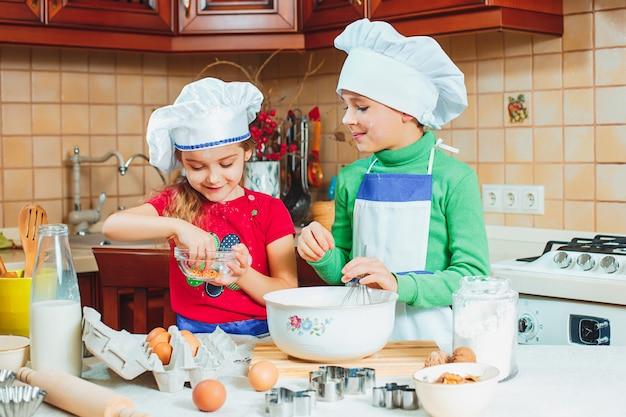 De gelukkige twee grappige kinderen bereiden het deeg voor, bakken koekjes in de keuken