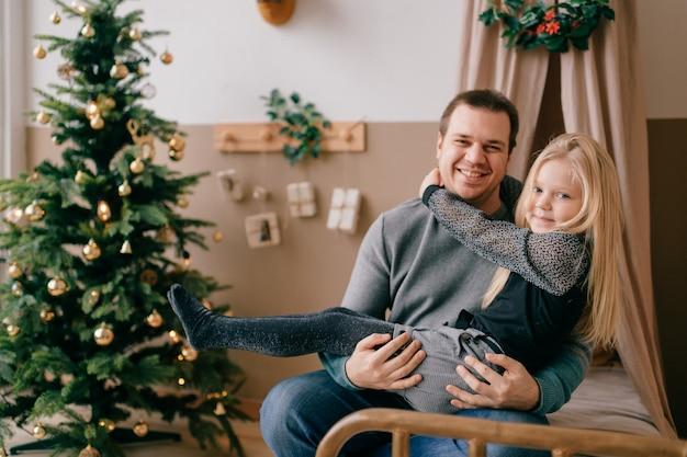 De gelukkige vader en de mooie dochter omhelzen elkaar in zoyruimte met cristmasboom en kinderenwigwam.