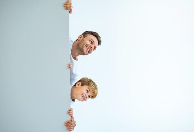 De gelukkige vader en een zoon staan achter de muur