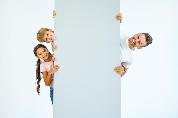 De gelukkige vader en kinderen staan achter de muur
