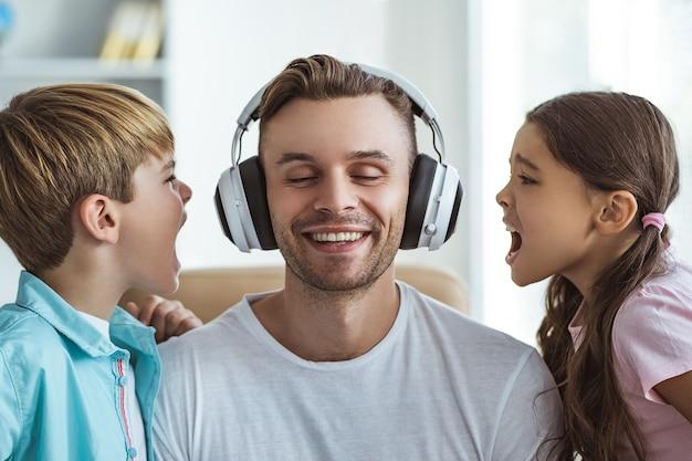 De gelukkige vader in koptelefoon speelt met een jongen en een meisje aan tafel
