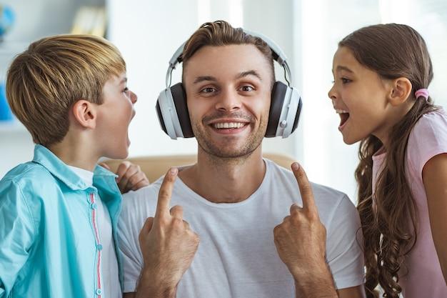 De gelukkige vader in koptelefoon spelen met een jongen en een meisje aan de balie