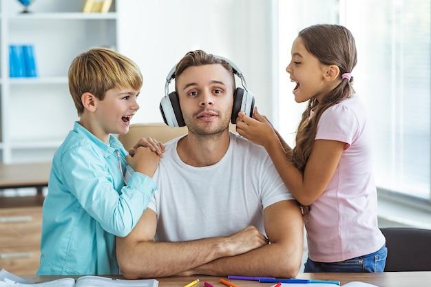 De gelukkige vader in koptelefoon zit met een jongen en een meisje aan de balie