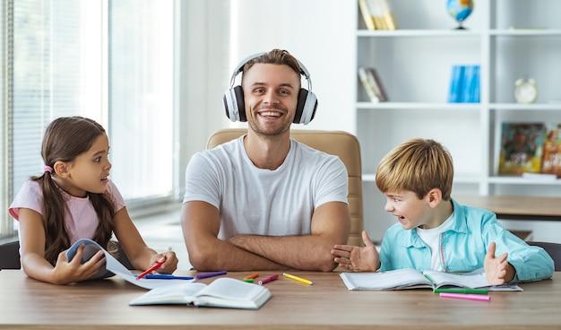De gelukkige vader in koptelefoon zit met kinderen aan de balie