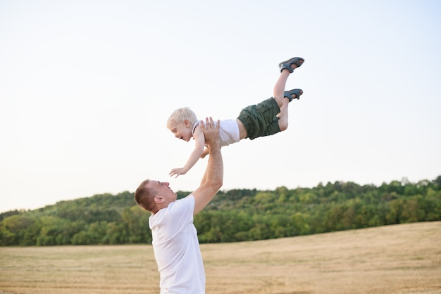 De gelukkige vader werpt omhoog een kleine blonde jongen op een gemaaid tarwegebied. zonsondergang tijd