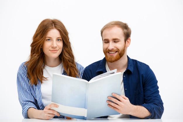 De gelukkige volwassen roodharige broers en zussen zien er oud fotoalbum uit