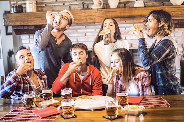 De gelukkige vrienden groeperen het eten van pizza bij het huis van het chaletrestaurant