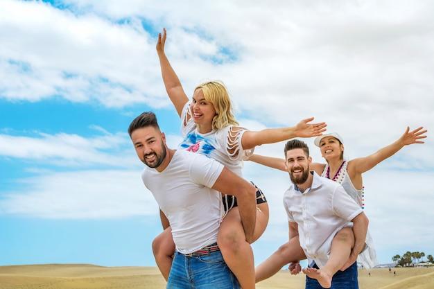 De gelukkige vrienden groeperen zich op hun vakantie aan het strand