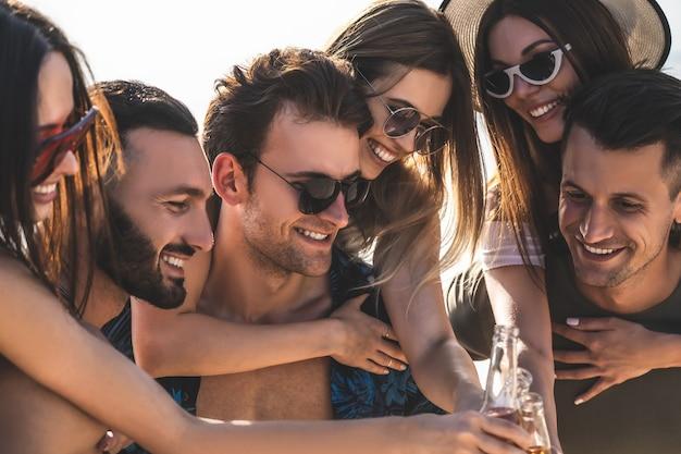De gelukkige vrienden klinken flessen buiten