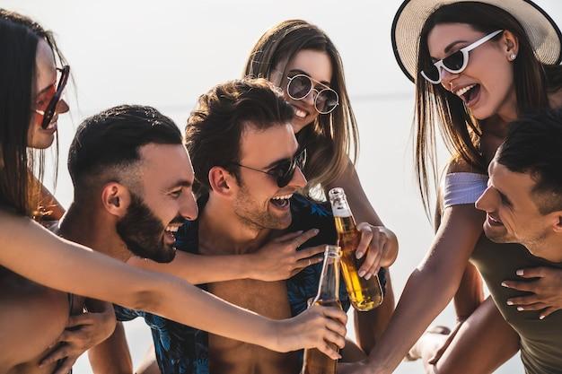 De gelukkige vrienden met flessen genieten van de zomer op het strand