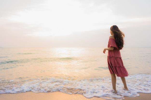 De gelukkige vrije tijd van de portret mooie jonge aziatische vrouw gelukkige op het strandoverzees en de oceaan