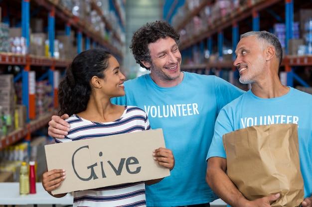 De gelukkige vrijwilliger glimlacht en kijkt elkaar