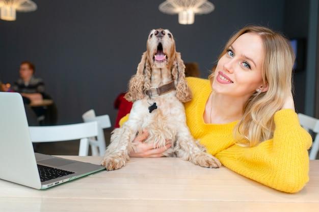 De gelukkige vrolijke blondedame koestert haar grappige cocker-spaniëlhond bij de lijst met laptop
