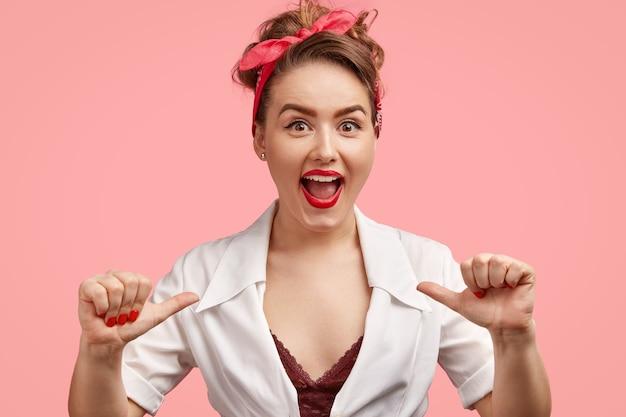 De gelukkige vrolijke positieve vrouw wijst op zichzelf