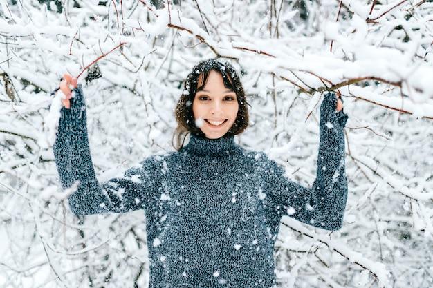 De gelukkige vrolijke tiener heeft de winterpret in de winterbos. mooi positief meisje schudden takken bedekt met sneeuw.