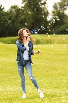 De gelukkige vrouw die bellen blaast in het park