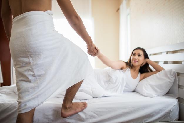 De gelukkige vrouw die de man bekijkt toont striptease in de slaapkamer