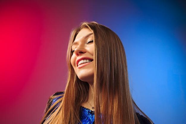 De gelukkige vrouw die en zich tegen gekleurde muur bevindt glimlacht