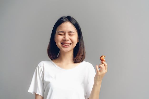 De gelukkige vrouw die gebraden kip houden voor eet.