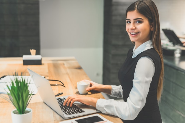 De gelukkige vrouw die koffie drinkt en met de laptop werkt