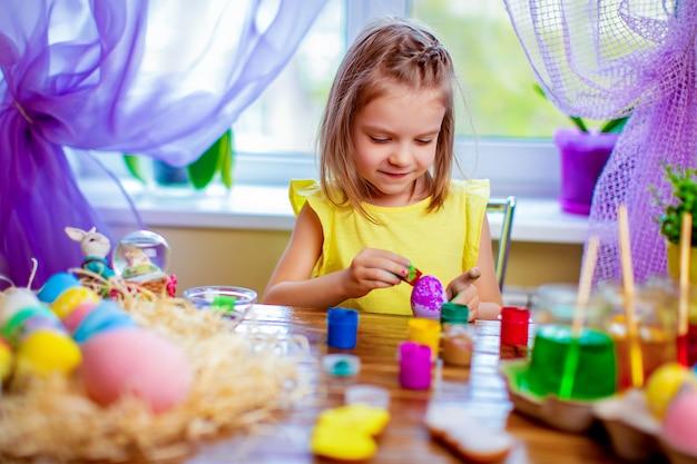 De gelukkige vrouw die paaseieren schilderen, heeft het kleine kind thuis pret. lente vakantie