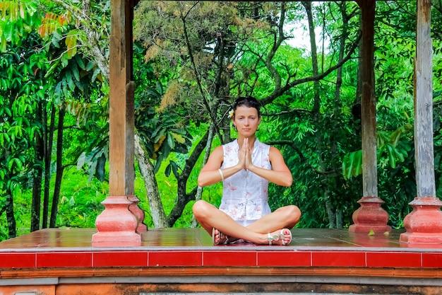 De gelukkige vrouw die yoga doet oefent openlucht uit