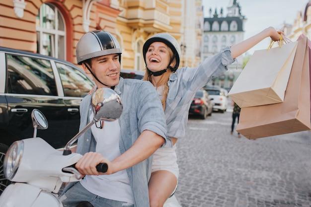 De gelukkige vrouw houdt het winkelen zakken in de hand en geniet van wit zijn vriend een motorfiets drijft