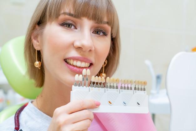 De gelukkige vrouw in de tandheelkunde pakt de kleur van tandglazuur op