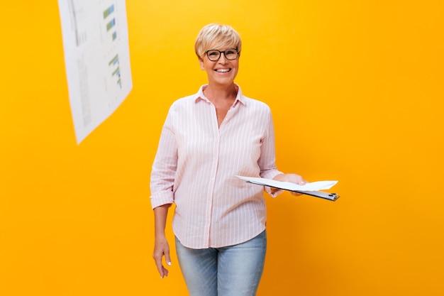 De gelukkige vrouw in gestreept overhemd en oogglazen stelt met documenten op oranje achtergrond