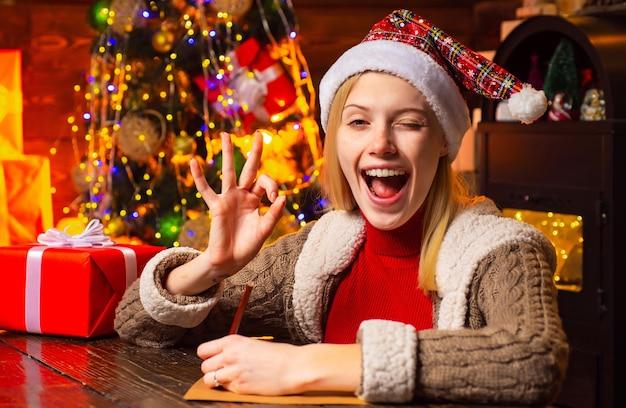 De gelukkige vrouw is klaar voor kerstavond. nieuwjaarsstemming. aantrekkelijke vrouw in een kerstkamer.
