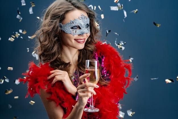 De gelukkige vrouw kijkt weg in een venetiaans masker bij een partij op een feestelijke achtergrond met klatergoud