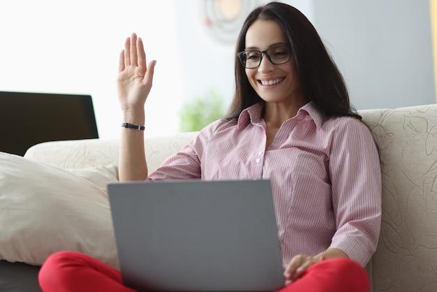 De gelukkige vrouw met bril bekijkt laptop en zwaait hallo