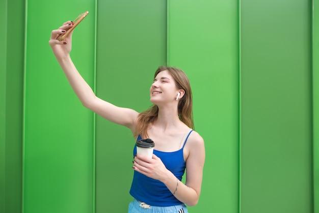 De gelukkige vrouw met een kop van koffie in hun handen en draadloze hoofdtelefoons op een achtergrond van groene muren maakt selfie. girk neemt selfie op een groene achtergrond
