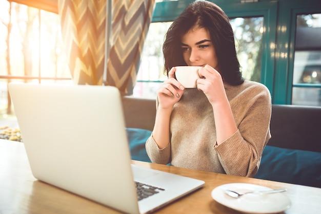 De gelukkige vrouw met een laptop drinkt een kopje koffie in een café