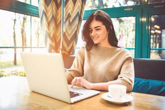 De gelukkige vrouw met een laptop zit in een café