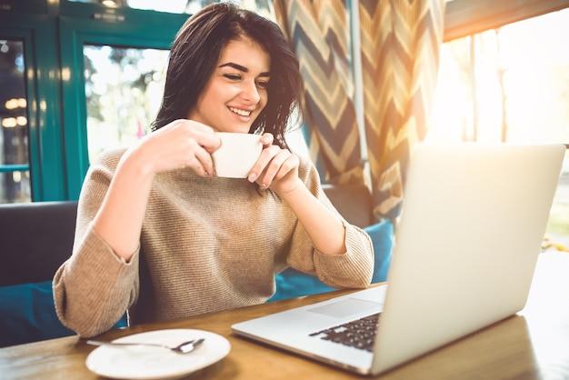 De gelukkige vrouw met een laptop zit in een restaurant