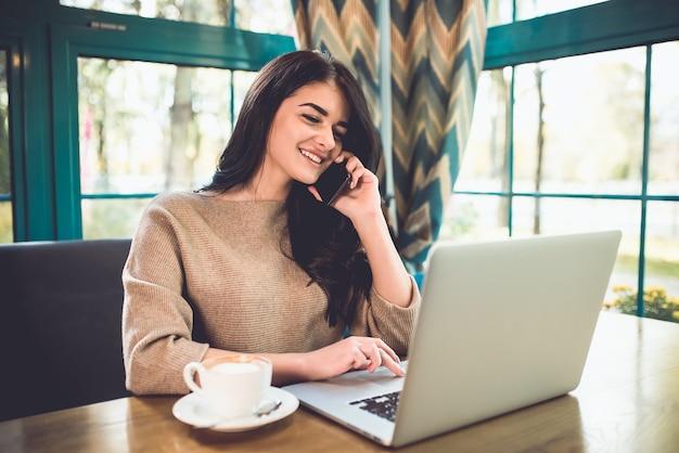 De gelukkige vrouw met een laptoptelefoon in het restaurant