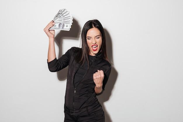 De gelukkige vrouw met rode lippen die geld houden maakt winnaargebaar.