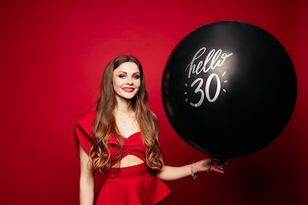 De gelukkige vrouw met zwarte luchtballon zegt hallo 30